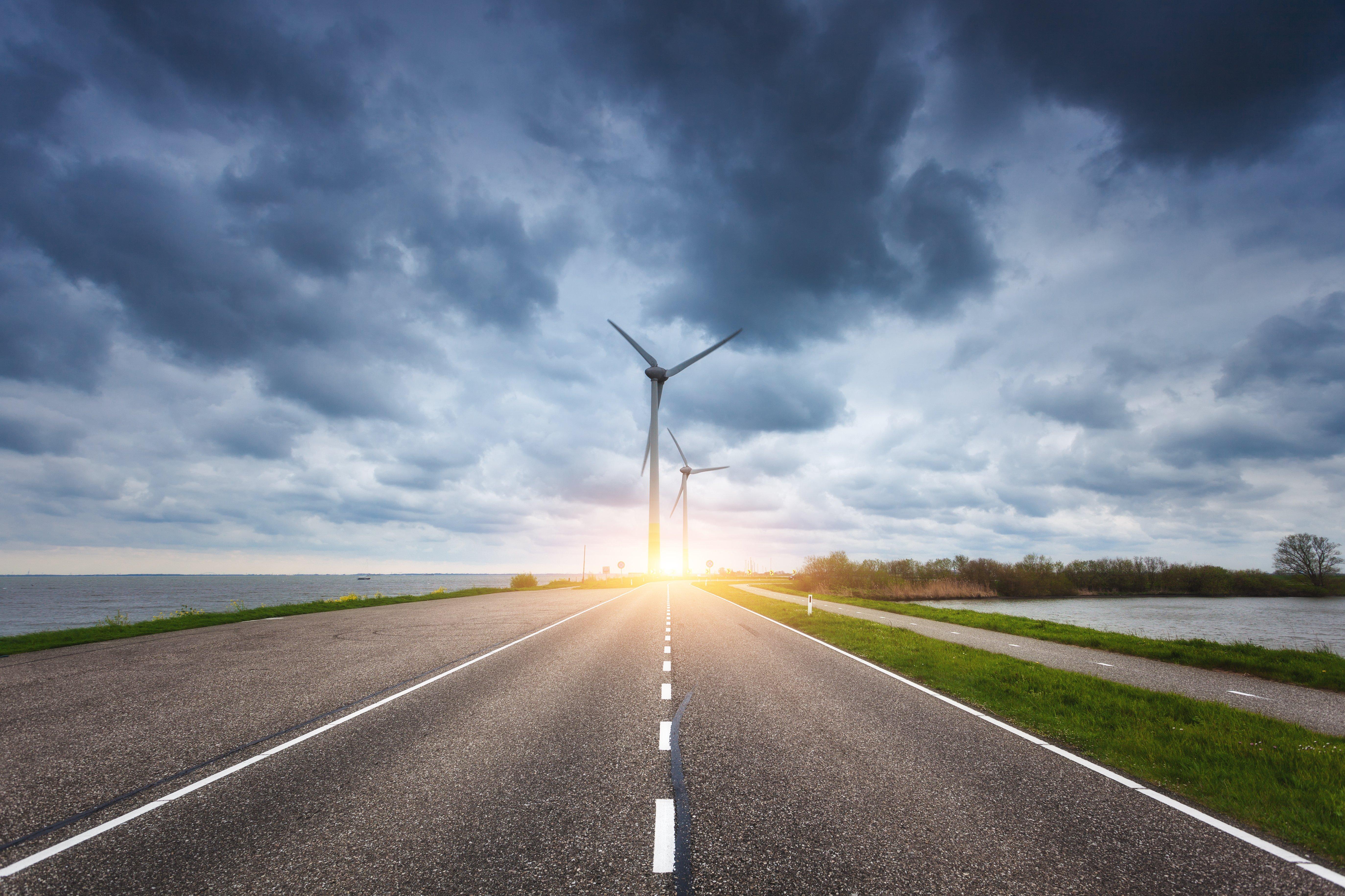 aslphalt road leading to wind turbines